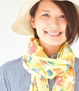黄色の花柄UVカットストールを巻く女性