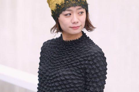 マスタード色のヘム レース デザイン ワッチをかぶる女性