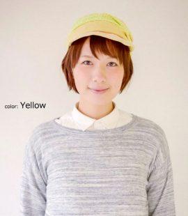 黄色のCABINデザインキャスケットをかぶる女性